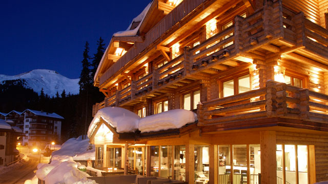 Exterior view of the Lodge at night with snow covered roofs.