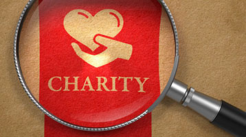Magnifying glass over a symbol for charity