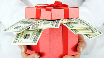 Red gift box overflowing with cash