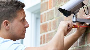 A man installs a security camera