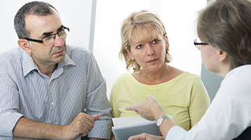 Spouses talking with an advisor