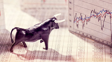bull figurine and market charts