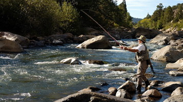 fly fisherman wading in a river