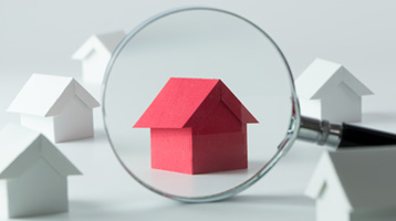 Little house magnified by magnifying glass